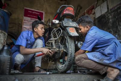 Boys repair a motorcycle at a workshop in Bangladesh.