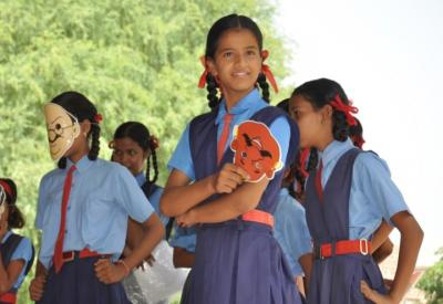 Girls participate in a performance at a school in India.