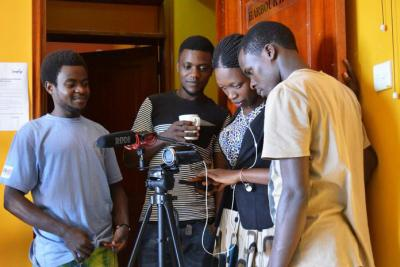 Four young people stand behind a camera as they learn skills in multimedia.
