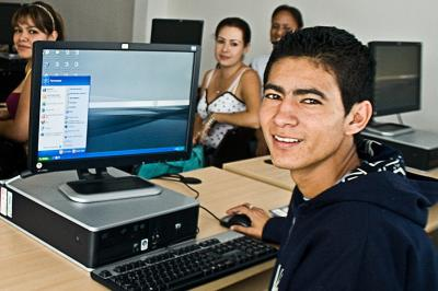 A young man uses a computer in Mexico, turning to face the camera.