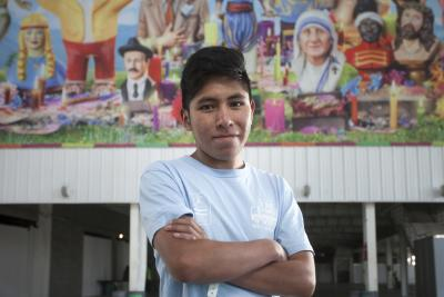 A young male student stands against a brightly coloured mural on a wall on Argentina.