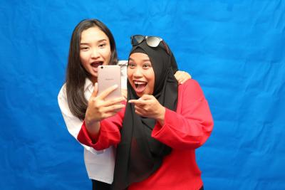 Two young women look into a mobile phone with big smiles.