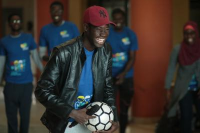 A young man holds a microphone and football as he laughs..