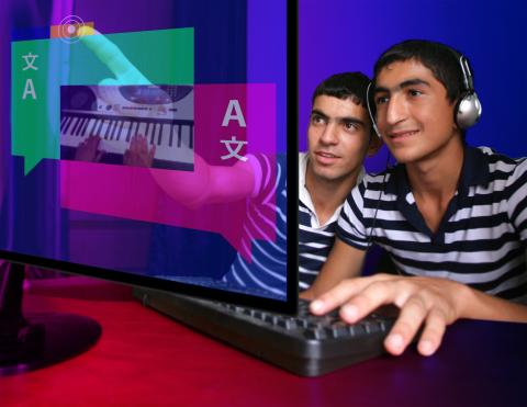Two boys use a computer together in Azerbaijan.