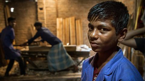 Mohammed, 15, stands in the lumber room of a woodworking shop in Cox's Bazar, Bangladesh.