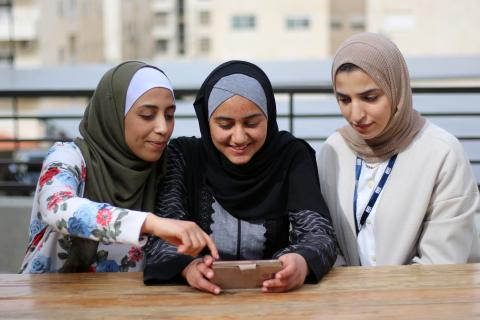 Three young women sit together in Jordan, looking at a mobile phone.