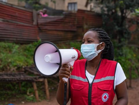 A volunteer with a red velvet Red Cross jacket is speaking on a megaphone