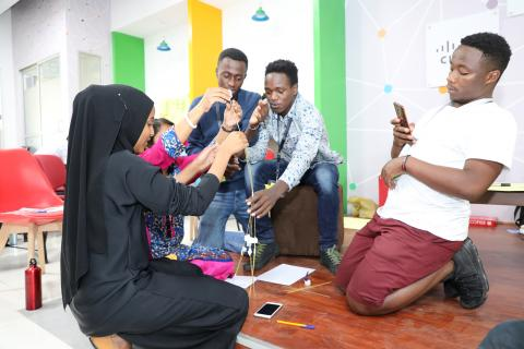 Young people collaborate in a workshop.