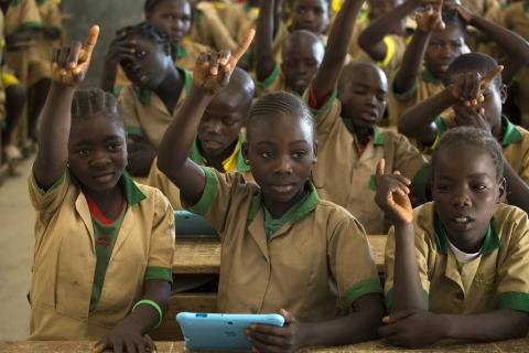 Twelve-year-old Waibai Buka (centre), holding a computer tablet provided by UNICEF, raises her hand to answer a question at a school in Bagai, northern Cameroon, Tuesday 31 October 2017.