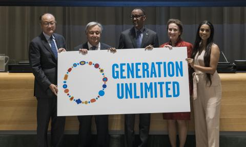 Five leaders stand together, holding a Generation Unlimited sign.