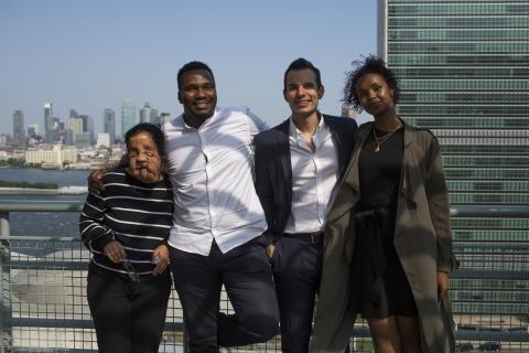 Four members of the Generation Unlimited Board pose for a photo in front of the United Nations in New York City.