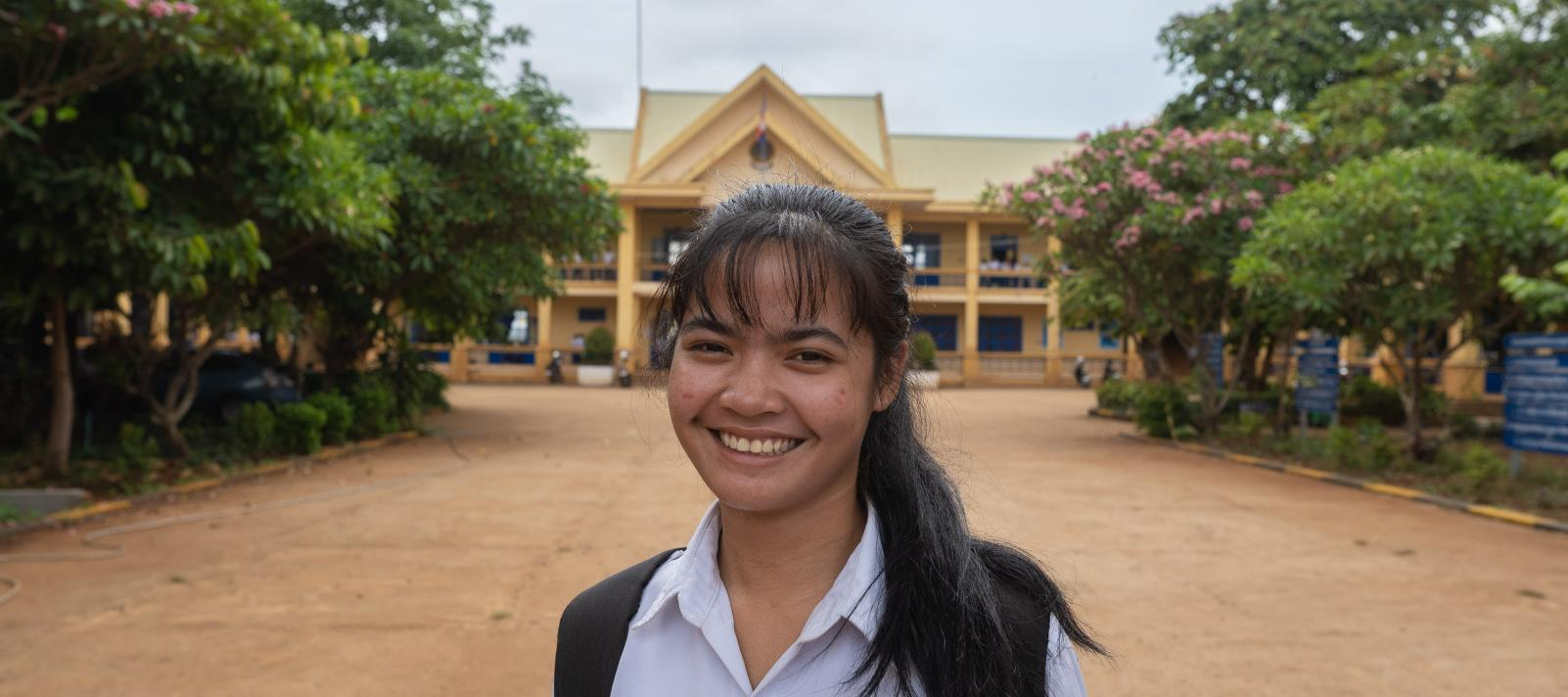 Channy Soy, 18, smiles brightly in front of her school. Channy is currently a grade 12 student and an indigenous ethnic minority scholarship recipient at Krong Banlung Boarding Secondary School, Thmar Da Village, Sangkat Beung Kansaeng, Banlung City, Ratanakiri Province.