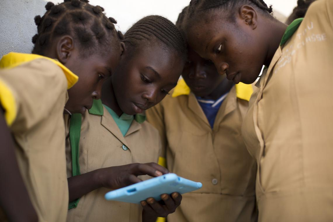 Four students crowd around a tablet, paying close attention in Camerooni.