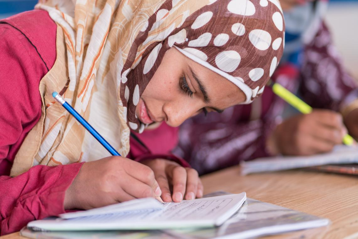 Wa'ed, a Syrian girl, writes in her notebook during class at a refugee camp in Jordan.