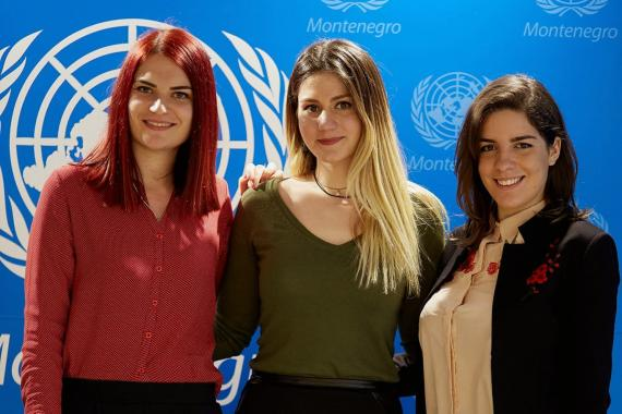 Three young women in Montenegro pose in front of a United Nations sign.