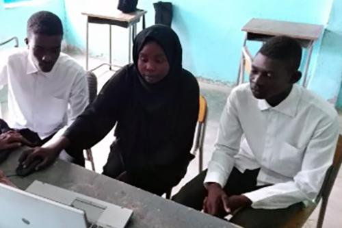 A team of three young people sits together at a computer.