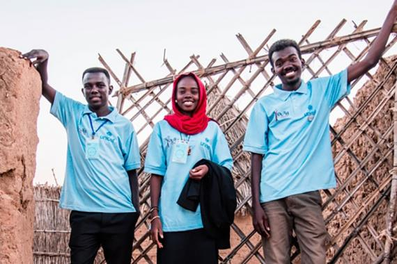 The Muntjatna team stands together outside by a fence, smiling.
