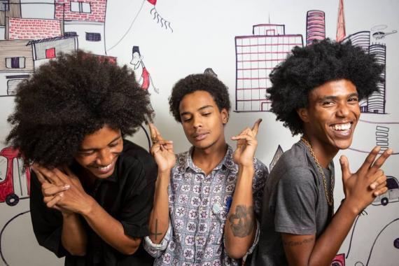 Three young people - members of Produção PRETA - laugh as they pose for a photo.