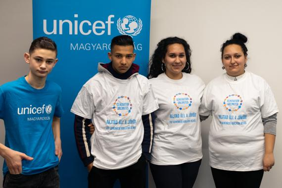 Four young people stand in front of a UNICEF sign.