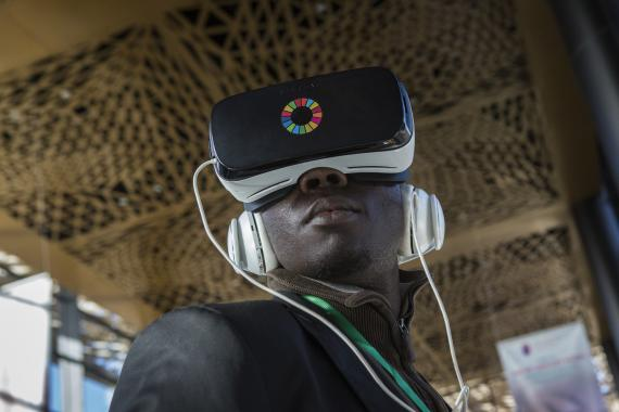 Journalist Babacar Fall, wearing a headset, watches a virtual reality video at the UNICEF exhibition at the Global Partnership for Education (GPE) Financing Conference in Diamniadio, Senegal