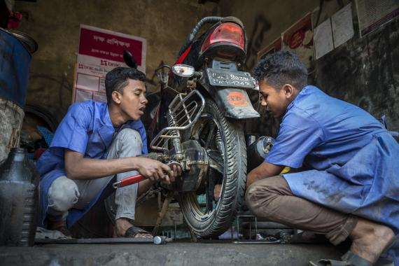 On 20 February 2019 in Bangladesh, (left-right) Mohammed Forhad and Biplob Barca, both 18 years old, work on a motorbike in a garage in Court Bazar, in the Cox's Bazar district.