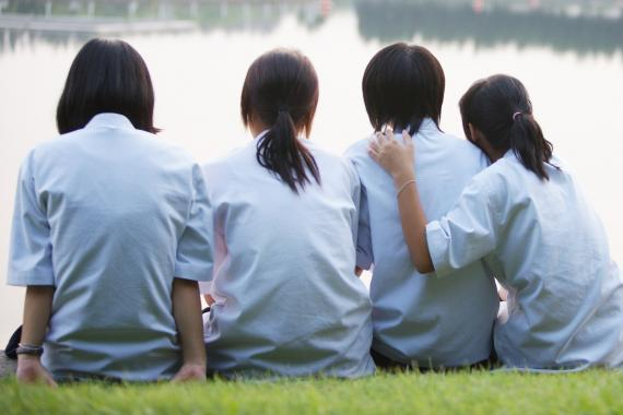 Four girls sit together on grass, with their backs to the camera, as they look out over water.