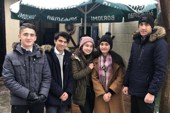 The five members of Youth Discovery stand together outside under a large umbrella, wearing warm winter clothes.